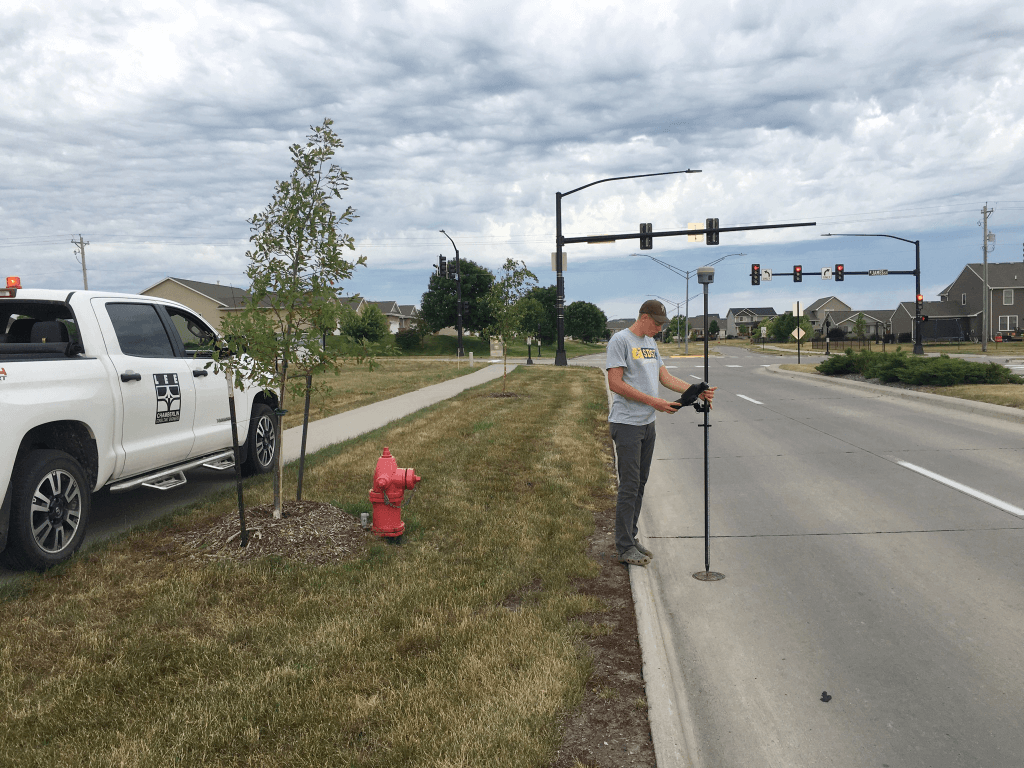 A LEE Chamberlin technician is performing an engineering survey on a city road.